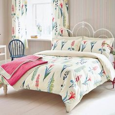 This contempory take on a botanical print features a pattern of naively drawn foliage and wild meadow flowers, in a lively palette of fresh blue and green tones that are accented with brighter notes of raspberry.