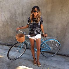 Browse these blogger-approved ways to pose with a bicycle at @Stylecaster | @sincerelyjules1 in printed blouse, white cutoff shorts, flats