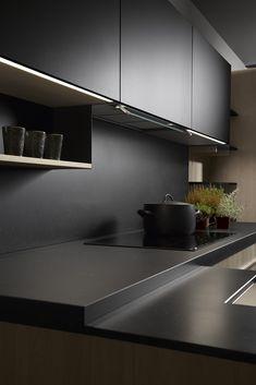 Les éléments noir et chêne en bois, se croisent et se confondent tout en formant une délimitation des zones techniques et un jeu de volumes inégalés.