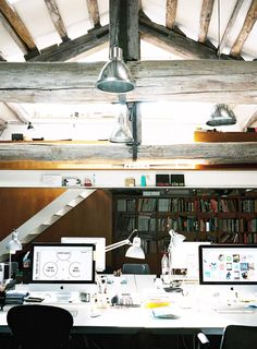 Office space with white desks, desktop computers, wood beams, wood bookshelves, and silver light fixtures