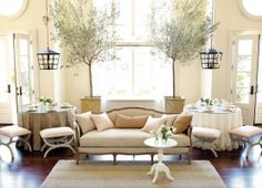 Flax sofa in a living room with high ceilings and tons of natural light