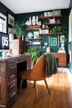 Moody office with walls painted in Benjamin Moore's Hunter Green. Medium-wood furniture like the desks and shelves add warmth. The modular shelves add storage as well as eclectic style.