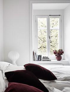 Trois petits coussins en velours bordeaux apportent une touche automnale à la chambre