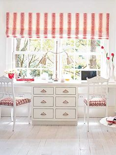 A small space off the kitchen provides room for a home office. The color scheme is borrowed from the kitchen, with a red print on the window treatment and the chair covers, and nickel hardware for polish. (Photo: Jeremy Samuelson)