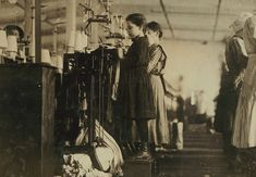 A little girl needs a box to reach the machine for her job as a knitter at a factory in Loudon, Tennessee in 1908