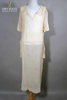 A long, peach-coloured, voile dress with short sleeves and a matching belt. Grey Roots Museum & Archives Collection.