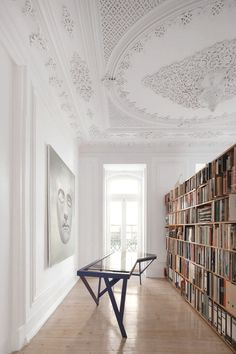 Love this room, with its ornamented ceiling, the elongated unusually-shaped table, and the bookcase segmenting it.