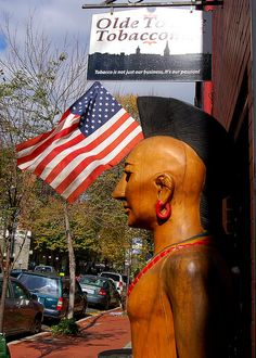 A cigar store Indian stands in the historic district of Fredericksburg, Virginia American Indians, Native American, Mohawk Indians, Cigar Store Indian, Ship Figurehead, Cigar Shops, Cigar Art, Totem Poles, Old Glory