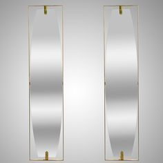 Pair Italian Mid Century Narrow Modernist Brass Mirrors In The Style of Gio Ponti  --  Pair circa 1970s Italian mirrors feature tall, narrow ovoid shaped mirrors with brass floating-style frames. Sold and priced as a pair. Good vintage condition with some wear consistent with age and use.  --   Item:  7284  --  Price:   $4295