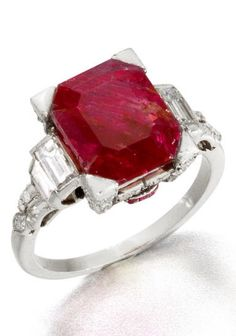 An Art Deco ruby and diamond ring, circa 1930. The octagonal step-cut ruby, weighing 6.49 carats, the mount decorated with single and baguette-cut diamonds and calibré-cut ruby accents. #ArtDeco #ring