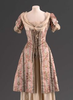 """Woman's jacket 1912–13 Woman's at-home jacket in the form of an 18th-century riding coat with deep skirts, made of pink, white and ivory satin stripes brocaded with polychrome flowers in the Louis XVI style, gold lame """"vest"""" with rhinestone buttons, ivory silk chiffon """"fichu"""" wraps around neck and hooks onto self on proper right; short puffed sleeves with chiffon """"engageantes."""""""