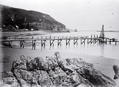 Construction of the Sumner Pier, Christchurch : looking from Cave Rock past the Sumner Hotel to Clifton Spur and Shag Rock. Christchurch New Zealand, City Library, Cave, Construction, Rock, History, Country, Beach, Places