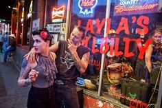 "Nashville in Neon, 2010 - Photograph by Will Van Overbeek - ""This two-block strip of Lower Broadway is the hottest spot in Nashville if you're there to hear music,"" says photographer Will van Overbeek. ""There's all this great neon and people walking across the street with stand-up bass fiddles. This couple was working that rockabilly look."""