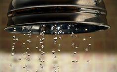 Gotas de agua justo cuando abrimos el grifo de la ducha. Al fondo, los azulejos del cuarto de baño difuminados. Comprar esta fotografía: http://photoconceptblog.wordpress.com/category/aguas-y-fluidos/
