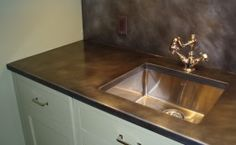 A zinc countertop with dark patina finish and undermount sink cutout. Polished nickel faucet and stainless sink.