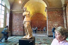 Visitors swirl around a statue (Aphrodite of Melos/Venus de Milo) in the Sully Wing of the Louvre Museum.