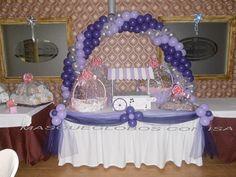 Mesa con arco de globos en tonos lilas.