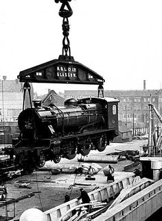 Steam locomotive being loaded aboard ship by the Finnieston crane, 1930s