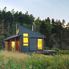 With a shed roof and corrugated siding, this off-the-grid cabin, beautifully sited on an island off the coast of New England, runs on solar power. A rainwater tank with an instant hot-water heater provides drinking and bathing water, while rolling exterior door panels protect the home in inclement weather. It may be tiny, but this house can stand tall all on its own