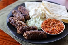 Cevapi or ćevapčići is a type of Kebab made out of grilled minced meat or pork, beef and or lamb served in with a flat bread with chopped onions, sour cream and ajvar (red bell pepper relish). Bosnian Cevapi Recipe, Bosnian Recipes, Croatian Recipes, Bosnian Food, Pepper Relish, Bell Pepper, Greek Meatballs, Macedonian Food, Paprika Pork