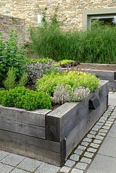 raised beds made of new railway sleepers which have weathered-down to a silvery-grey. Like the double row of granite setts.