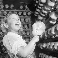 c. 1955 A girl looks at doll's heads at a factory on Long Island. IMAGE: ORLANDO /THREE LIONS/GETTY IMAGES