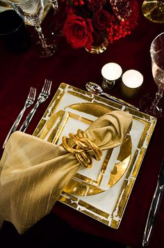 A luxurious gold holiday dinner napkin is styled with a chic holder for added elegance.  Bright or antique gold organza napkins, garland, and table overlays as well as napkin rings, coasters, and wine covers available at alwayselegant.com