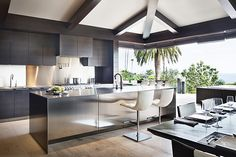 A sleek, indoor-outdoor kitchen by Philip Nimmo supplants a formal dining room in this Laguna Beach, California vacation home. Pocket doors and dark-colored cabinetry were nods to Balinese design.