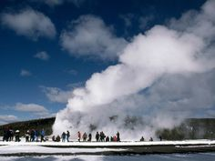 Photograph by Raymond Gehman    Tourists look on as Old Faithful, Yellowstone National Park's most famous geyser, sends a tower of scaling water skyward. Recent research suggests the clockwork geyser eruptions are slowing down—and may even stop—due to global warming-related dry spells.