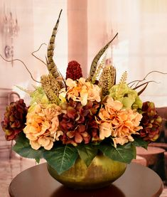 A unique floral design  made in an burnished copper and gold finish metal  bowl.  Filled with lush hydrangeas in burgundy and warm tan shades.  Accented with feathers. Pods and branches.