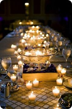 floating candles alternating with lots of votives; I saw you pinned this as well--the vase is sitting on a base of flowers. Would you like just the bowl with candles better?