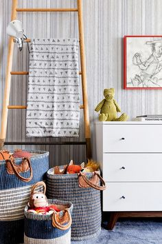 Toys and blankets are arranged in woven baskets and layered on a whimsical…