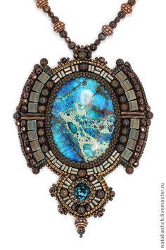 Кулон. В кулоне использованы тонированный варисцит, кристалл Swarovski, японский бисер Toho и Miyuki, металлические бусины TierraCast, бусины из природного камня - бронзита, бусины из чешского стекла. Изнанка выполнена из натуральной кожи телесного цвета. Длина шнура 54 см, длина кулона 9,5 см, ширина до 7 см.