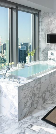 Infinity tub surrounded by marble looking out on a beautiful city view.