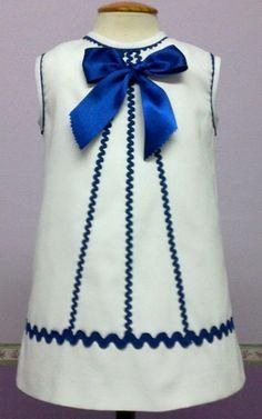 Vestido de bebe niña de pique de canutillo blanco con piquillo y lazo azulino con lazo a juego.