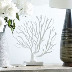 Shaped like sea coral, this Coral Tree is made of enamel-coated metal and set on a marble stand. Display it on desks, consoles or mantles for a modern, beachy look.