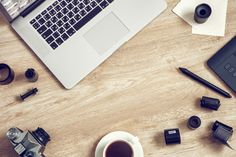 #Work space for photographer  Work space for freelancer photographer retoucher designer: laptop retro camera film rolls digital tablet and coffee cup. Retro toned photo.