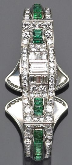 An art deco diamond, emerald and platinum bangle bracelet, circa 1930  of hinged design, the top centering a row of baguette-cut diamonds within old European-cut diamond concave borders and accented by calibré-cut emerald archs, the shoulders centering emerald rows within diamond frames and completed by a curved clasp detailed with diamonds; estimated total diamond weight