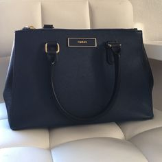 """DKNY Saffiano Leather Satchel (Navy + Black) Like new! The Saffiano leather is easy to maintain and is rain resistant. It can be carried with top handles or with detachable strap. Dimensions are approximately 11x8x4"""". Take a look at my closet for other great condition bags I'm retiring from my collection! DKNY Bags Satchels"""