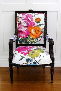 Traditional black chair frame comes alive with splashy floral fabric in pink, orange and green on a fresh white ground.