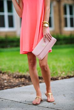 neon orange dress and pink clutch