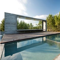 A glazed box supporting a pool and sundeck protrudes from the roof of this concrete holiday house in Argentina