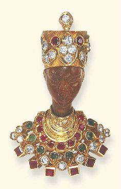 A MULTI-GEM AND CARNELIAN BLACKAMOOR BROOCH, BY NARDI  The carved carnelian blackamoor wearing a circular-cut diamond, ruby and emerald turban, and a similarly-set textured gold tunic with square-cut ruby trim, mounted in 18k gold