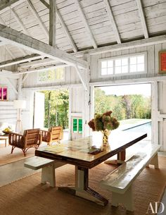 At a family's rural Connecticut estate designed by India Mahdavi, a barn was converted into a poolhouse, offering extra space for family and friends to gather. | archdigest.com