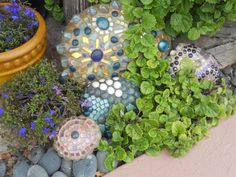 These would be fun crafts for me and girls...mosaic rocks and paint. Place in a swirl design on bark with plants in center?