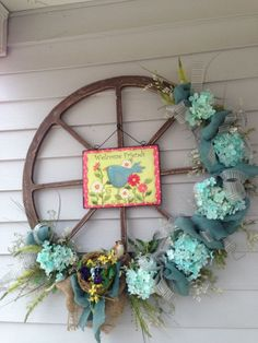 Easter Decorated Wheel Wreath. Wreath becomes a traditional way for Easter decoration with Easter egg, fresh flower, Easter bunny elements. What distinguishes this from other wreath is the floral decorated wheel. There is a picture hang in the centerpiece.