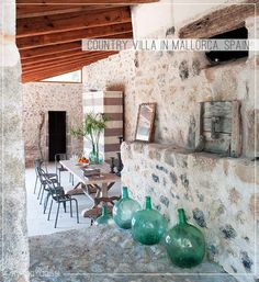 A country villa in Mallorca, Spain, with bare stone walls and pebble floors. Love the bottles - See more at www.myparadissi.com