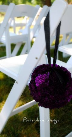 A pomander ball made of purple hydrangeas, purple ranunculus, purple anemones, and purple lisianthus will hang from the arch over the door of the Artisan Ballroom.