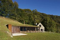 Extension Of A Barn / Earth green roof with stone house. Stone and metal construction