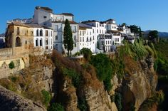 The Stunning Cliffside City of Ronda, Spain The city is situated in a very mountainous area about 750 meters (2,460 ft) above mean sea level. The Guadalevin River runs through the city, dividing it in two and carving out the steep, 100 plus meters deep El Tajo canyon upon which the city perches. Three bridges, Puente Romano, Puente Viejo and Puente Nuevo, span the canyon. The Puente Nuevo is the tallest of the bridges, towering 120 metres (390 ft) above the canyon floor. All three serve as…